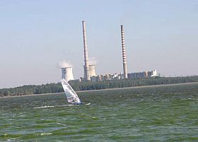 Industrial landscape with a windsurfer on a lake in the foreground. Two tall chimneys of a power plant. Strong wind.