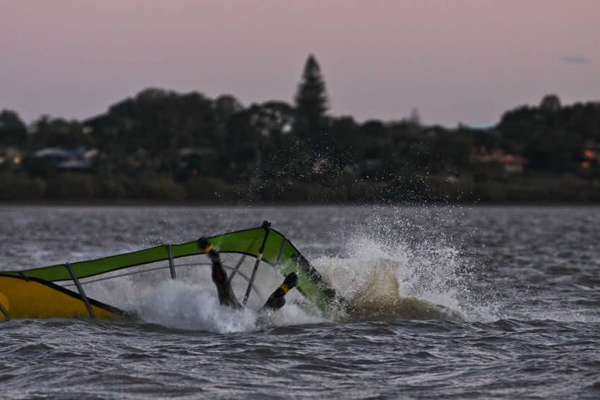 Windsurfer slipping during a manoeuvre, falls head first.