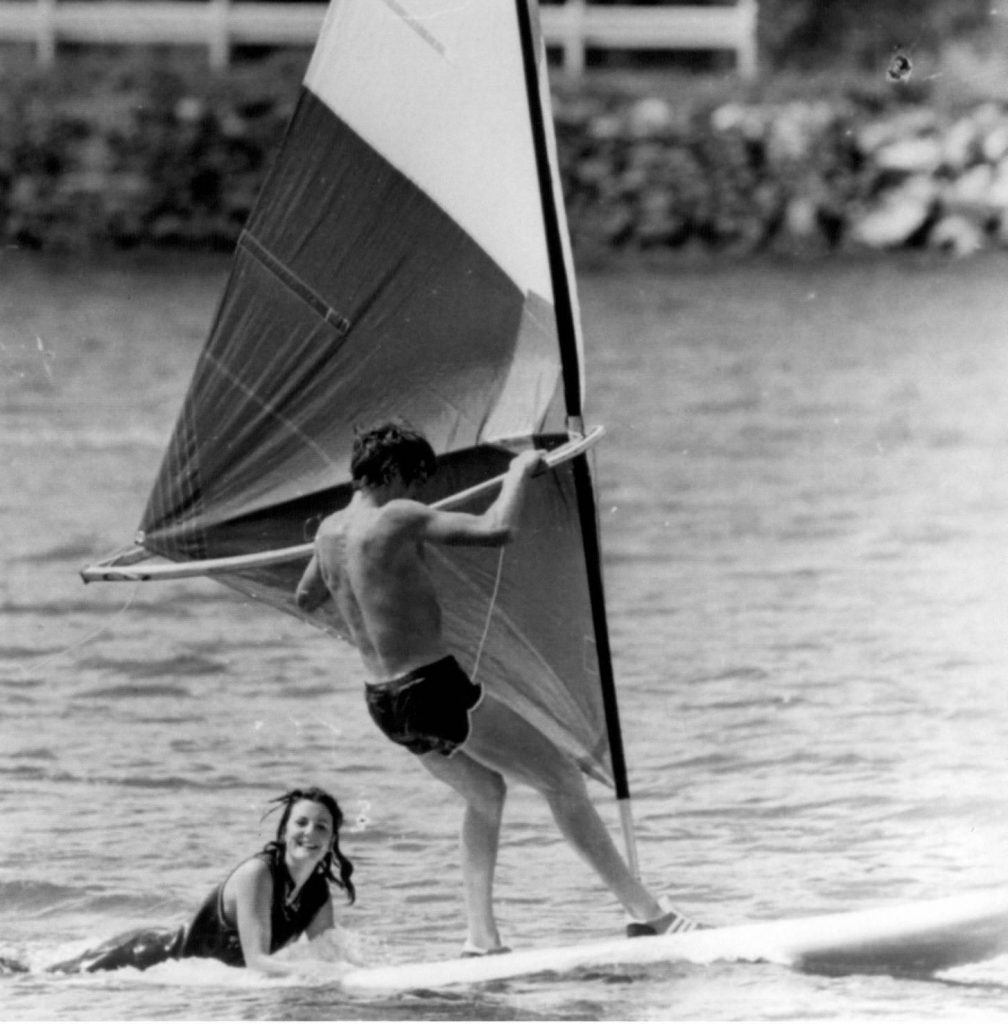 Old-school windsurfing board with a lady on the back.