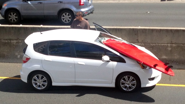 Surf board incident on a motorway. Board sticking through a smashed windshield, heavy damage.